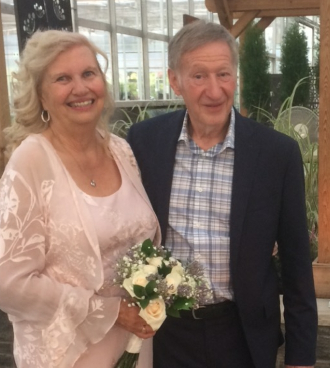 A beautiful mature Christian woman smiles next to her husband while holding her bouquet