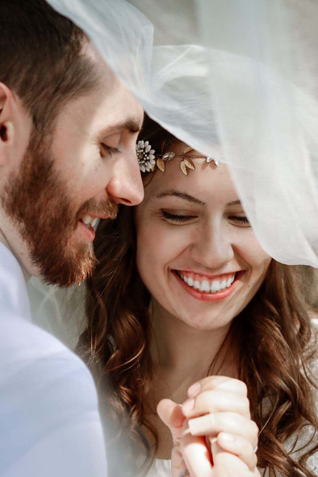 Christian bride smiles with her new husband while looking at her ring
