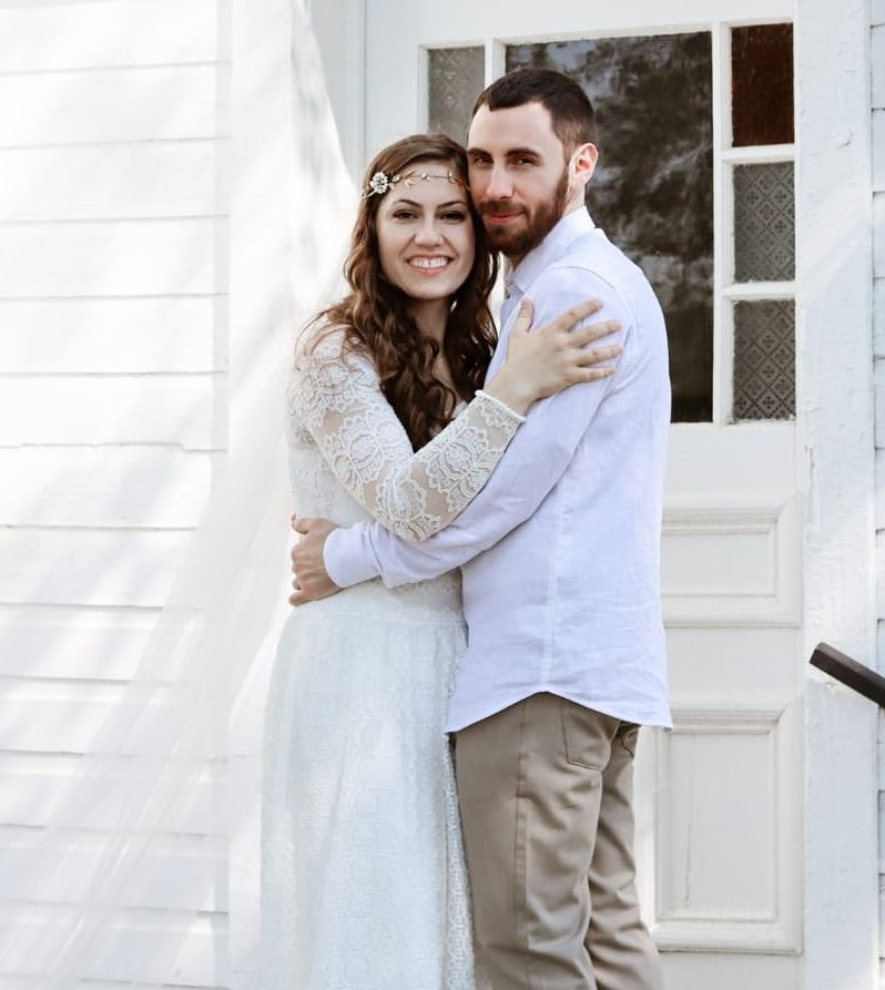 A handsome man hugs his beautiful new wife