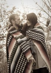 Former single Christians wrapped in ponchos gaze lovingly at each other outside