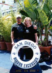 Widowed Christians hug behind a San Diego Harbor sign