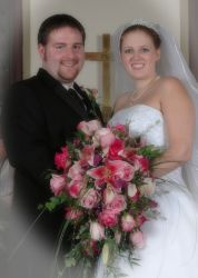 A wonderful Christian couple stand together in front of a cross, holding her wedding bouquet