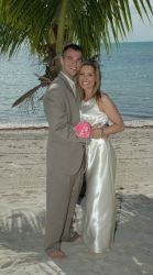 A beautiful Christian couple smile together on the beach under a palm tree