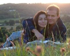 A couple hug and smile while lying in the grass at sunset