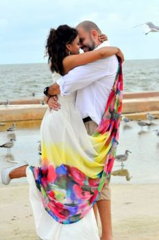 A Beautiful Christian single woman jumps up as a man kisses her on a beach