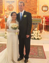 A tall White man stands next to his beautiful Asian wife, who smiles broadly