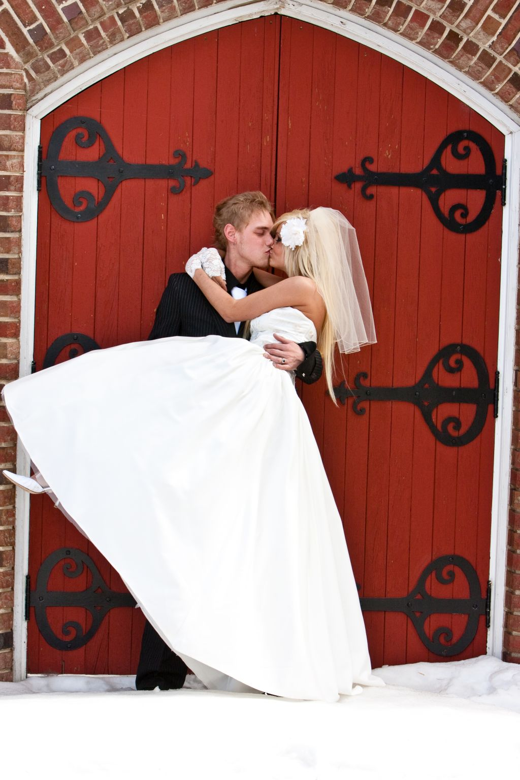 Groom carries his bride while kissing her lovingly