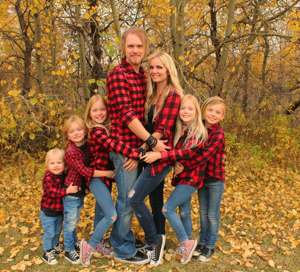 Family all dressed in lumberjack shirts smile in the cutest forest hug