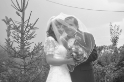 A joyful Christian couple smile shyly as they are united under her wedding veil