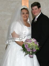 Born again Christian bride holds beautiful bridal flowers as she smiles joyfully next to her husband