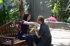 A man proposes on one knee to a young woman who is seated in a botanical garden