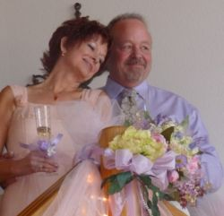 Christian wife looks so peaceful in the arms of her loving husband as she holds her wedding flowers