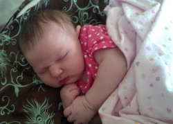 An adorable baby in pink sleeps with her blankie