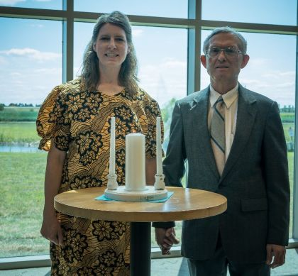 Former Christian singles from Illinois marry and pose in front of wedding candles in front of big glass windows