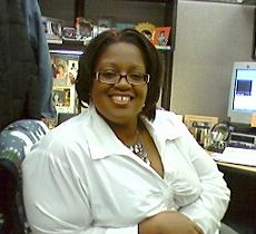 A woman with a beautiful smile sits at a computer desk