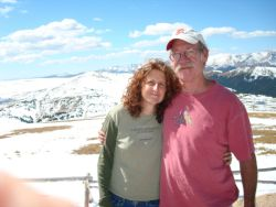 Mature Christian single is hugged by a man at a mountain lookout