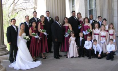 Huge wedding party flanks smiling Christian couple as they pose outside