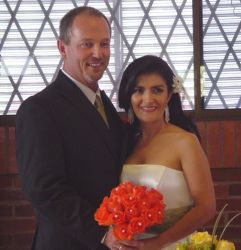 A Colombian Christian woman holds a beautiful wedding bouquet while standing next to her American husband