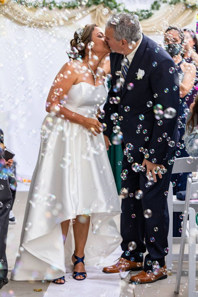 Wedding kiss at the altar, surrounded by soap bubbles