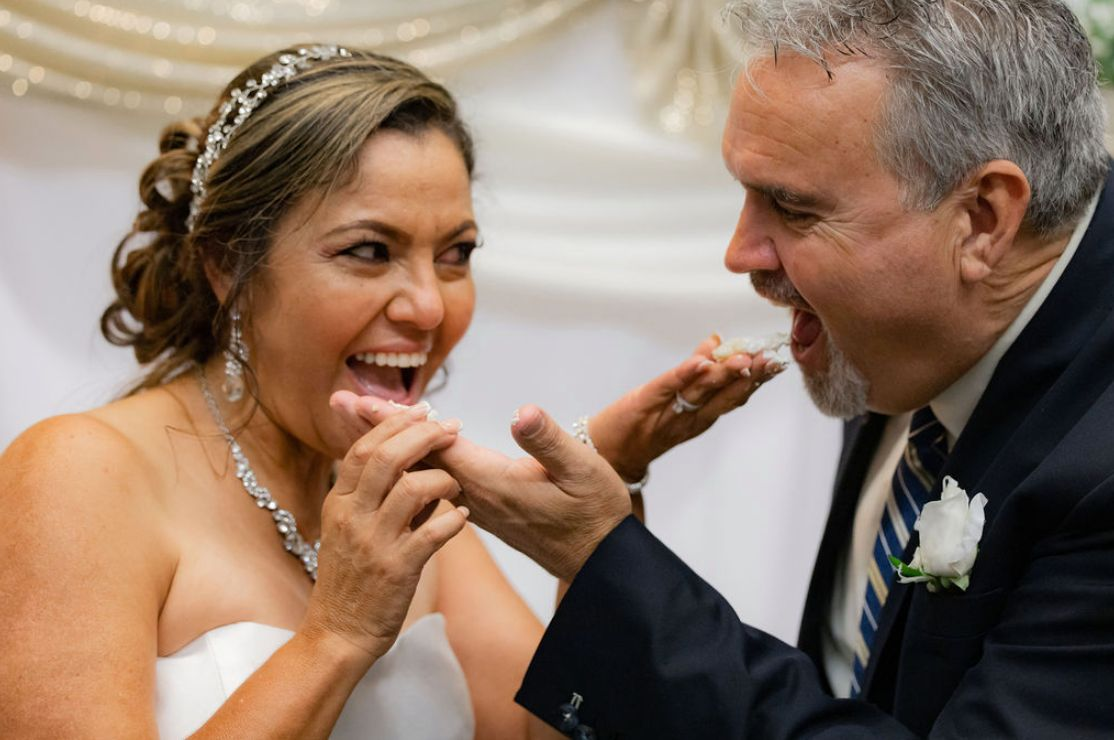 Newlyweds playfully feed each other cake while laughing