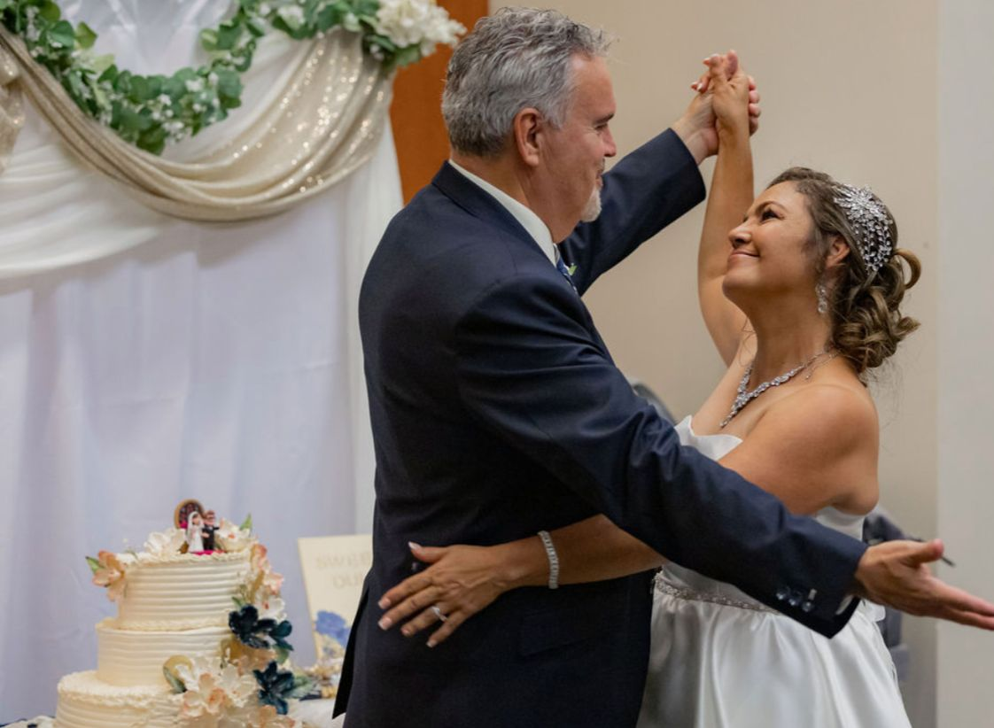 A bride gazes into her new husband's eyes as they dance