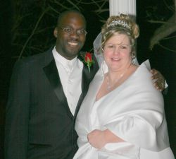 A very happy interracial couple smile and laugh on their wedding day