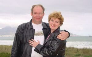 South African Christian singles hug and smile by the ocean