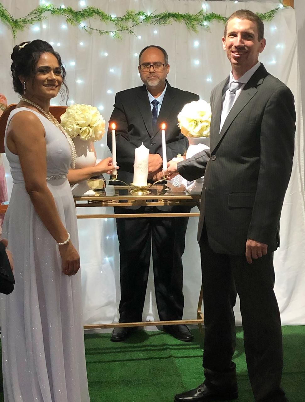 Brazilian bride in white dress lighting wedding candles with American groom