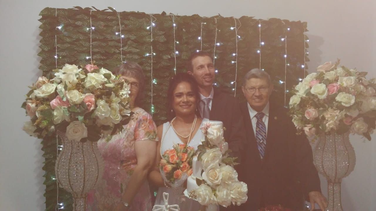 Family wedding shot including parents next to vases and bouquet of flowers