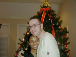 A pretty Black Christian woman smiles and hugs her new love in front of a Christmas tree