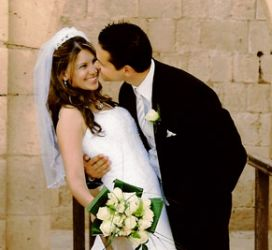 Canadian Christian leans in to kiss his Mediterranean bride who smiles broadly