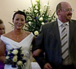 English groom beaming with joy as he walks arm in arm with his beautiful bride