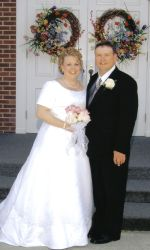 Newlywed Christians smiles together outdoors under wreaths of beautiful flowers
