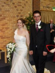An elated Christian bride holds her husband's hand and walks down the aisle with him