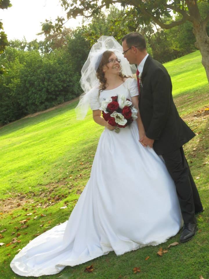 Former Christian singles now married gaze lovingly on the grass in sunshine