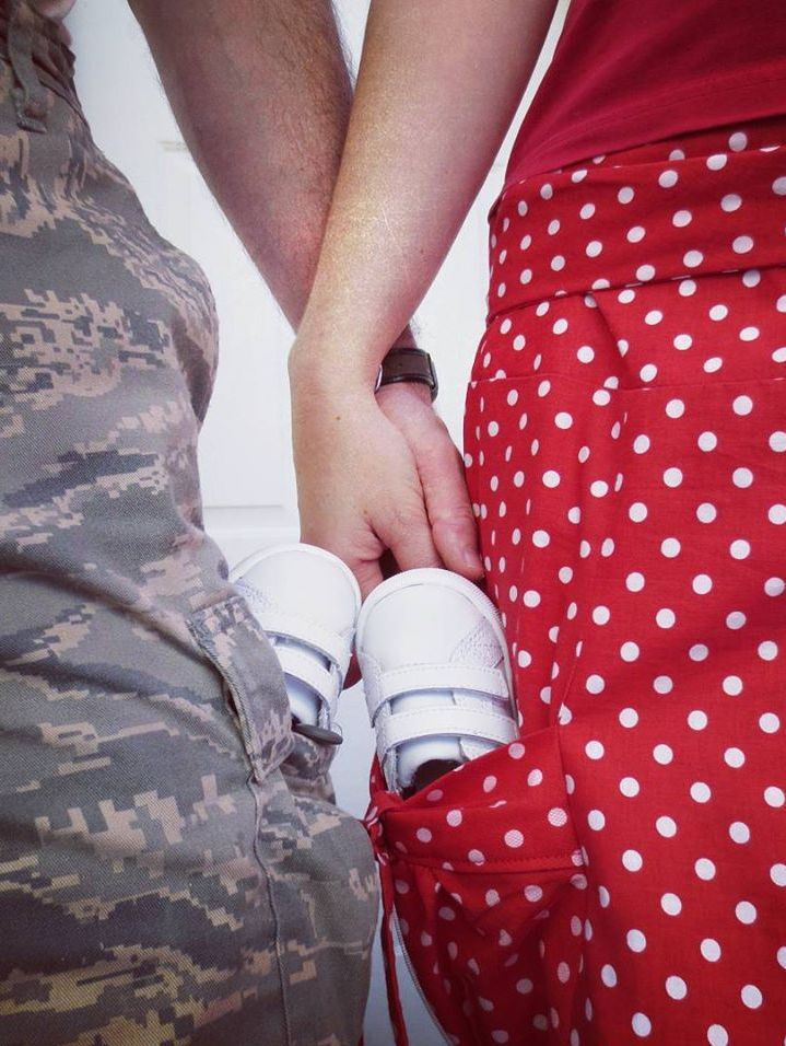 A couple holds hands as well as infant shoes in their pockets to symbolize her pregnancy
