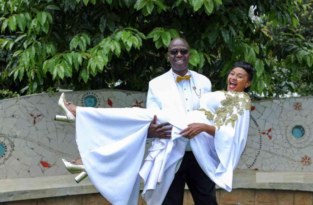Kenya Christian groom in white carrying his Kenyan bride as she laughs