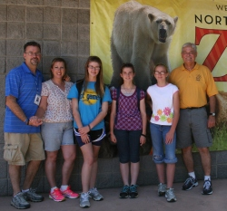A family poses against a wall outside the zoo