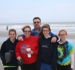 A North Carolina family with teenagers poses on a cold windy day at the beach