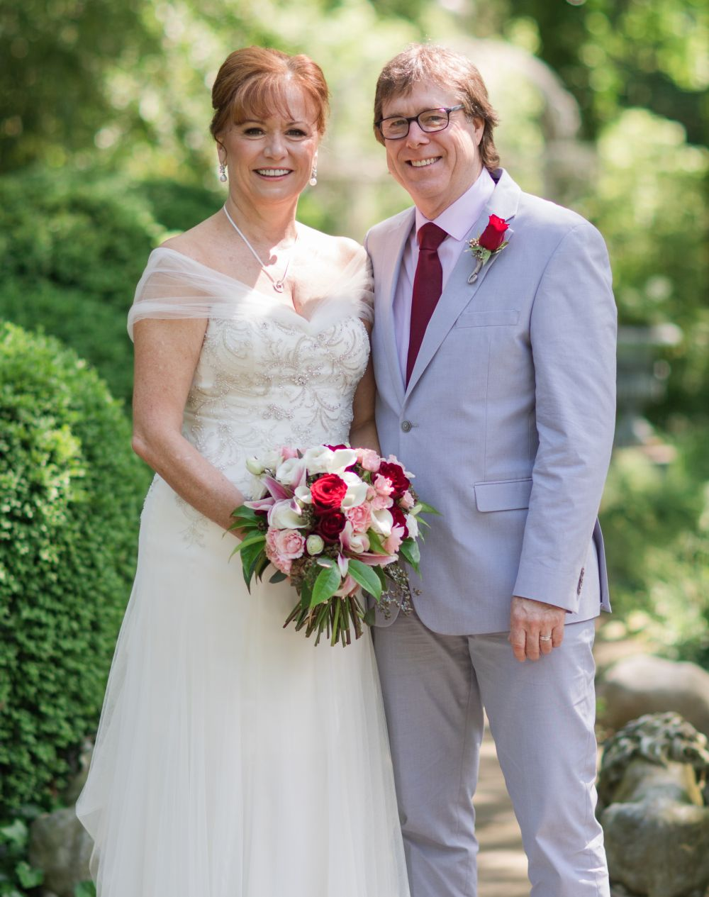 Delaware Christian woman poses in beautiful white wedding dress with husband, also from Delaware, and in pale blue suit