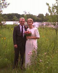 Senior Christians marry. Posing together in a field near a river