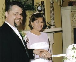 A man grins as he blindly pushes his wife's hand down as she tries cutting the cake