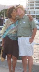 A woman kisses a man on the cheek near the beach in Cairns