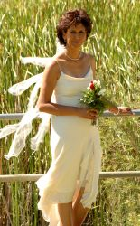 a beautiful bride pose in her wedding dress with flowers in front of a field