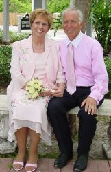 Christian runner sits hand in hand with his new wife, who smiles ear to ear