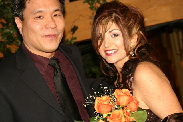 Former singles from Ontario smiling after marrying with beautiful orange bouquet