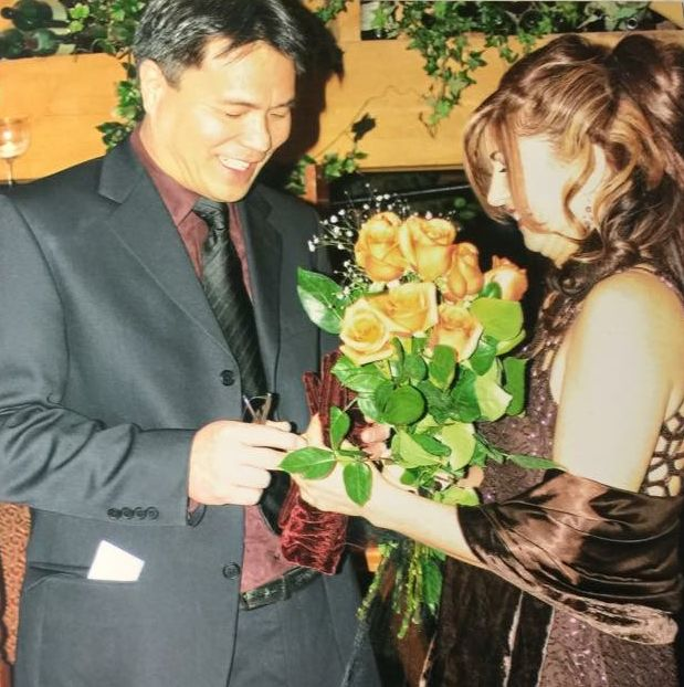 Putting on the wedding ring on his bride, with bouquet in foreground