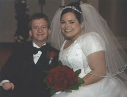 Online dating brought this happy Christian couple together. Shown smiling on their wedding day