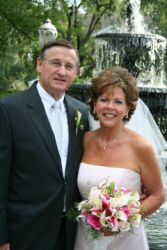 Southern Christian widower stands next to his beautiful new bride in front of a fountain