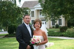 A newly married older Christian couple smile on their wedding day outdoors